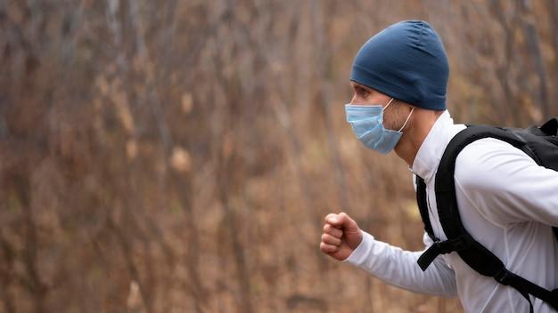 Portret van man met gezichtsmasker dat in het bos loopt
