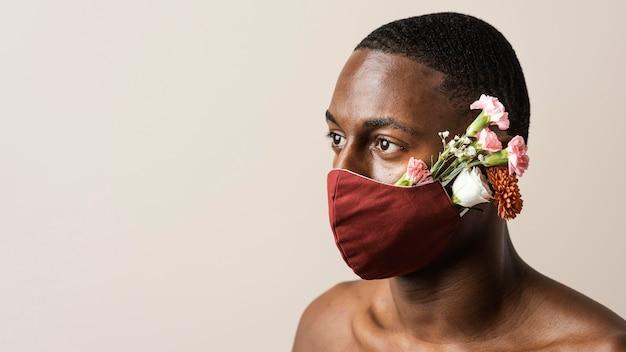 Portret van man met gezichtsmasker en bloemen met kopie ruimte