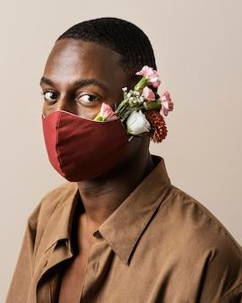 Portret van man met gezichtsmasker en bloemen