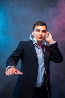 Portret van man met koptelefoon op donkere muur met rook