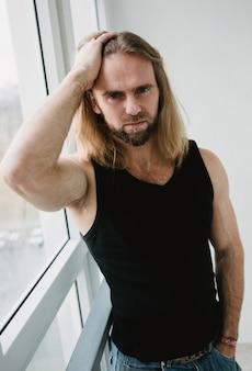 Portret van man met lang blond haar. close-upportret van het jonge jongen stellen in wit. brute stier met geweldige ogen raakt haar aan