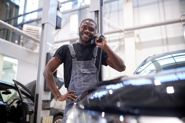Portret van man met machtsbuffermachine voor het polijsten van auto's