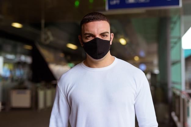 Portret van man met masker voor bescherming tegen uitbraak van het coronavirus sociaal afstand nemen op het skytrain-station