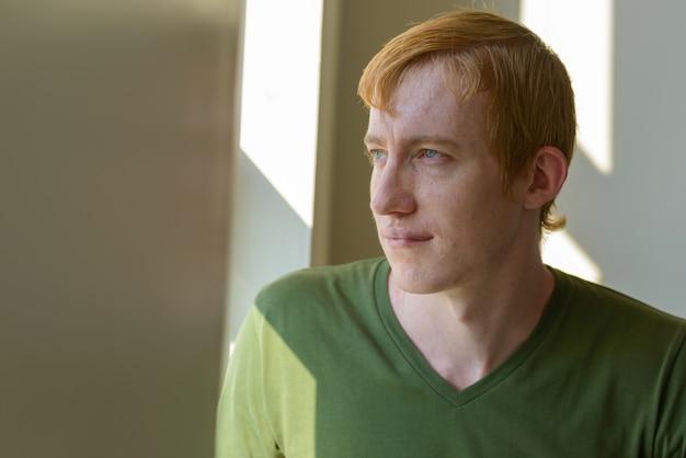 Portret van man met rood haar bij het raam thuis