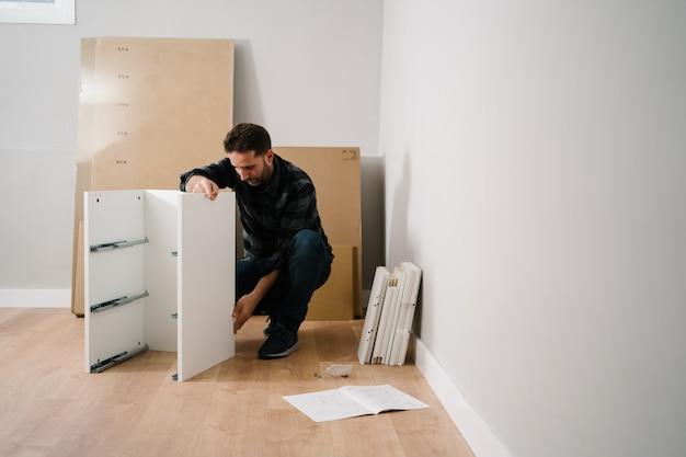 Portret van man meubels monteren. doe het zelf meubelmontage.