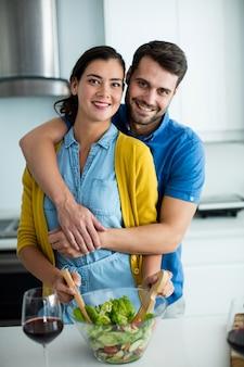 Portret van man omhelst vrouw in de keuken thuis