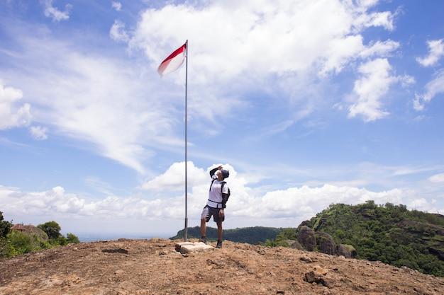 Portret van man op de top van de heuvel stijgende indonesische vlag vieren onafhankelijkheidsdag Premium Foto