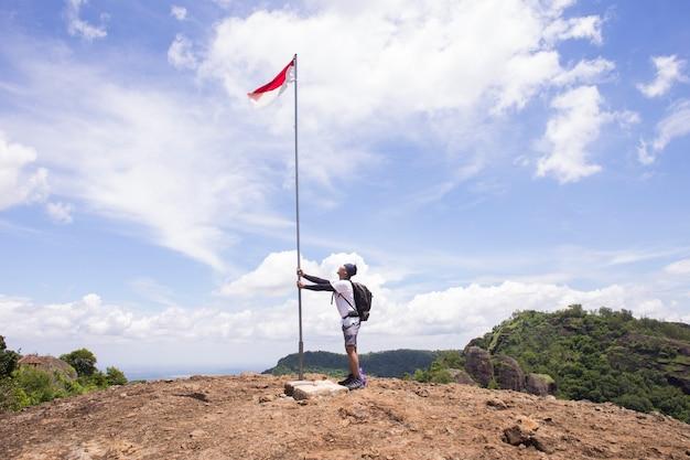 Portret van man op de top van de heuvel stijgende indonesische vlag vieren onafhankelijkheidsdag