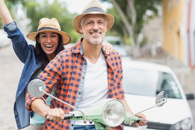 Portret van man rijden bromfiets met opgewonden vrouw
