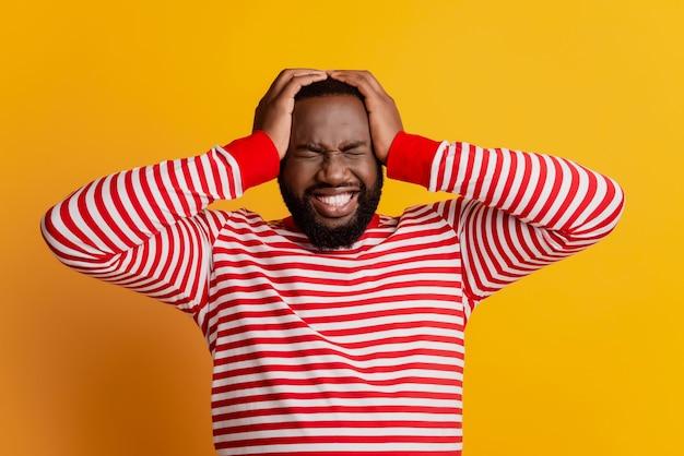 Portret van man touch head heeft migraine op gele muur