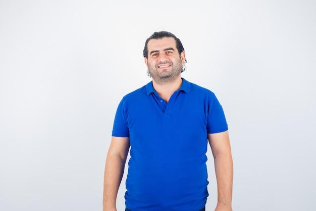 Portret van man van middelbare leeftijd die camera in blauw t-shirt bekijkt en gelukkig vooraanzicht kijkt