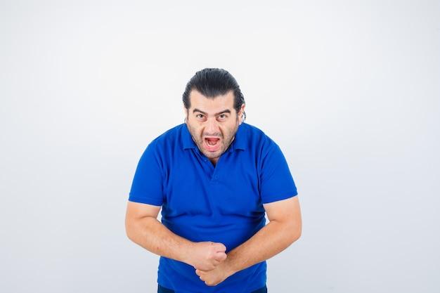 Portret van man van middelbare leeftijd houden handen op agressieve manier in blauw t-shirt en op zoek woedend vooraanzicht