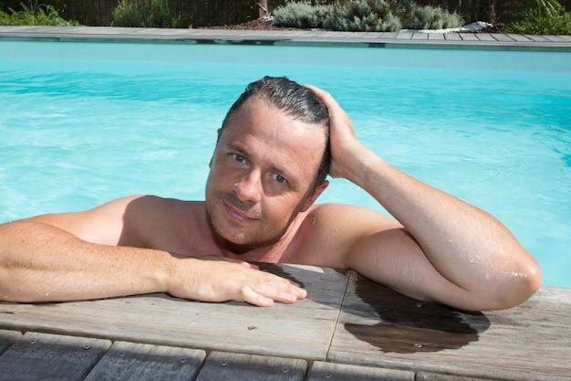 Portret van man van middelbare leeftijd met handen op het hoofd ontspannen bij het zwembad