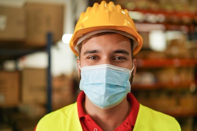 Portret van man werknemer in magazijn met veiligheidsmasker voor coronaviruspreventie