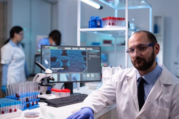 Portret van man wetenschapper in onderzoekslaboratorium op zoek