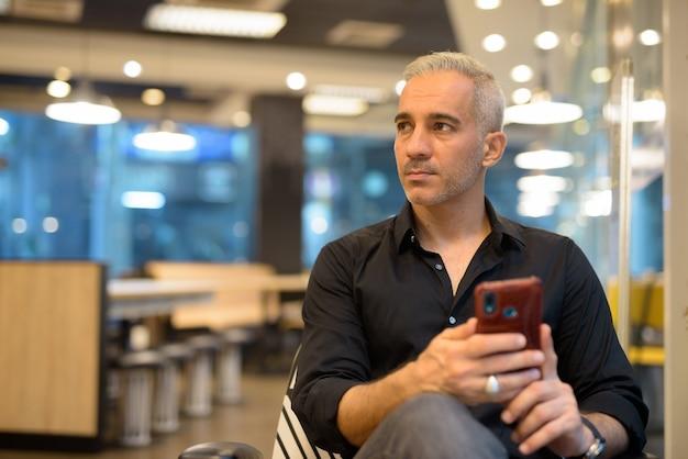 Portret van man zit in coffeeshop met behulp van mobiele telefoon en denken