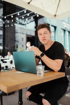 Portret van man zittend aan een tafel die werkt op een laptopcomputer.