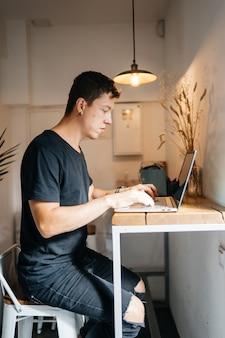 Portret van man zittend aan een tafel thuis werken op een laptop.