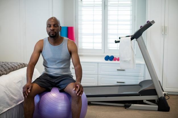 Portret van man zittend op fitness bal in slaapkamer