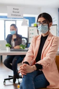 Portret van manager-ondernemer met gezichtsmasker als veiligheidsmaatregel tijdens de uitbraak van het coronavirus en houdt sociale afstand van collega's in een kantoorgebouw die naar de camera kijken.