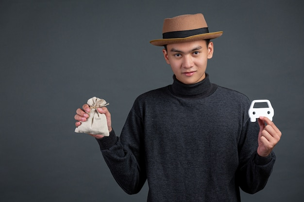 Portret van mannelijk model met zak munt en automodel op donkere muur