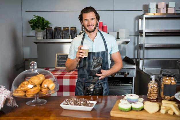 Portret van mannelijk personeel koffiekopje en koffiezak houden aan balie