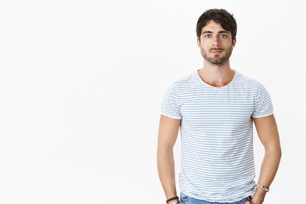 Portret van mannelijke aantrekkelijke europese man met blauwe ogen en borstelig, golvend haar grijnzend grijnzend hand in hand in zakken staande tegen grijze muur in gestreept t-shirt