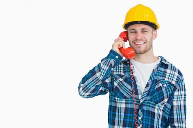 Portret van mannelijke architect die landline telefoon met behulp van