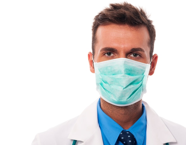 Portret van mannelijke arts die chirurgisch masker draagt