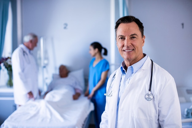 Portret van mannelijke arts die in de afdeling glimlacht