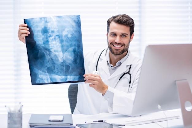 Portret van mannelijke arts die röntgenstraal onderzoekt
