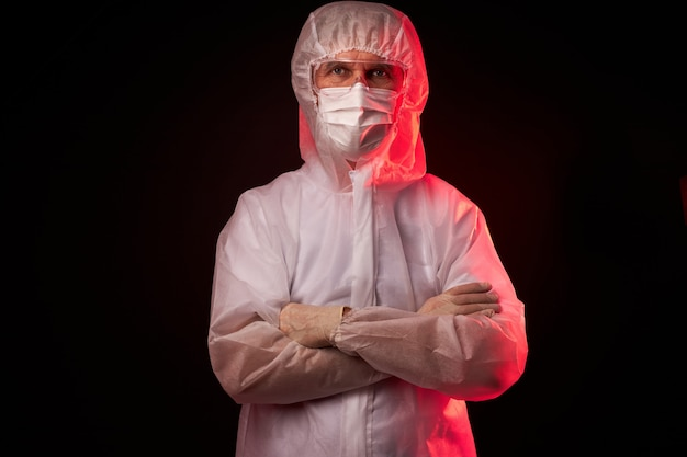 Portret van mannelijke arts in medisch pak poseren geïsoleerd op zwarte ruimte, waarschuwingsbord, mensen waarschuwen tegen het virus over de hele wereld, covid-19 concept