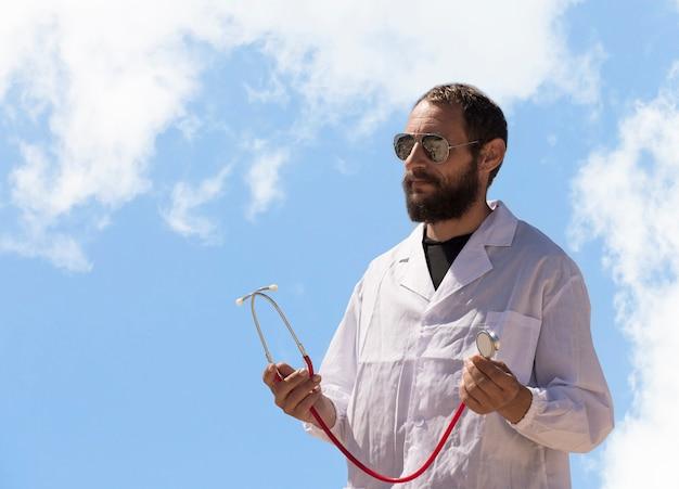 Portret van mannelijke arts met stethoscoop in de hand. amerikaanse knappe bebaarde man op blauwe hemelachtergrond. russische blanke brutale dokter in een witte jas en zonnebril. behandeling in israël, gezondheidszorg