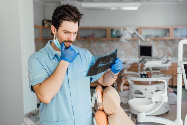 Portret van mannelijke arts of tandarts die naar röntgenfoto's kijkt, in zijn moderne kantoor.