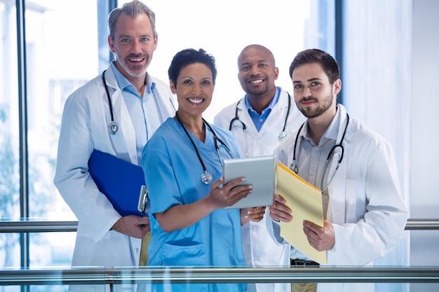 Portret van mannelijke artsen en verpleegster die digitale tablet in gang gebruiken
