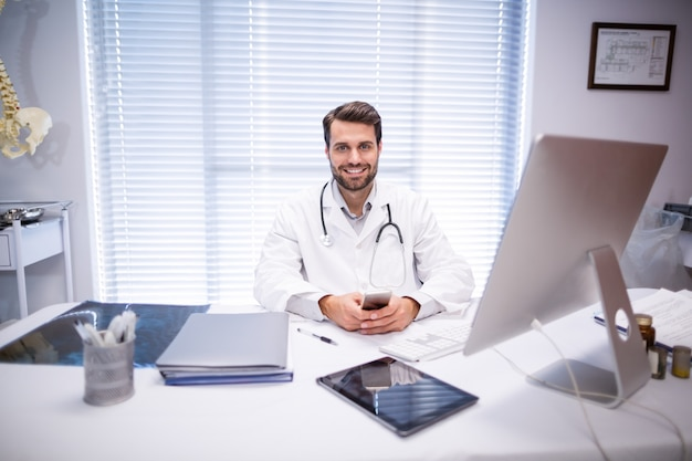 Portret van mannelijke artsenzitting bij bureau