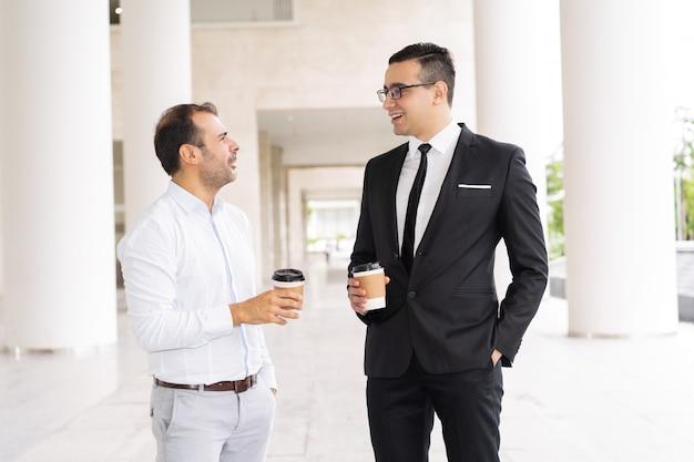 Portret van mannelijke bedrijfscollega's die koffie en het spreken drinken