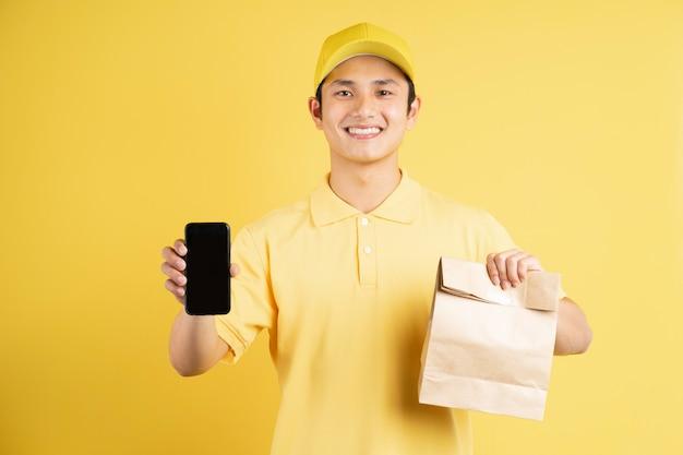 Portret van mannelijke bezorger met boodschappentas en telefoon