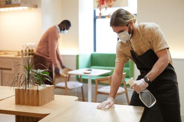 Portret van mannelijke cafémedewerker die een masker en gezichtsschild draagt terwijl hij tafels schoonmaakt en meubels schoonmaakt, kopieer ruimte