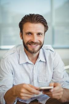 Portret van mannelijke directeuren die mobiele telefoon met behulp van