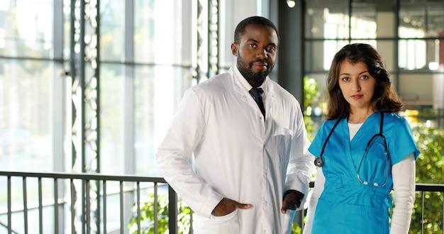 Portret van mannelijke en vrouwelijke artsen van gemengde rassen in uniformen die vreugdevol naar camera in kliniek glimlachen. multi-etnische man en vrouw, medici in het ziekenhuis. arts met verpleegster. doc en assistent. dolly neergeschoten.