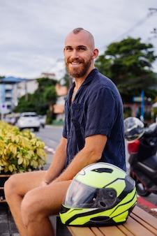 Portret van mannelijke fietser met gele helm zittend op een bankje aan de promenade in thailand op zonsondergang tijd