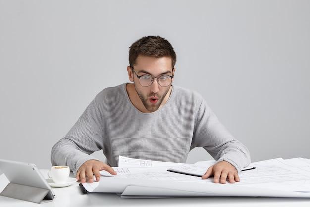 Portret van mannelijke ingenieur staart naar tekeningen, kijkt verbaasd, probeert te begrijpen wat er staat