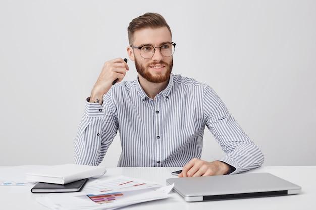 Portret van mannelijke kantoormedewerker, heeft een specifieke uitstraling, formeel gekleed, zit aan een wit bureau,