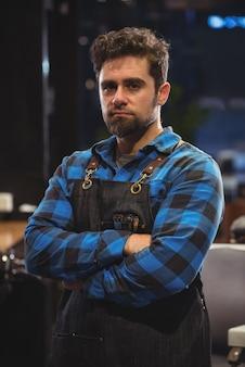 Portret van mannelijke kapper die zich met gekruist wapen bevindt