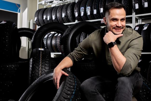 Portret van mannelijke klant omringd door vele autobanden keuze maken en kopen. zit alleen poseren voor de camera.