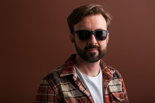 Portret van mannelijke knappe stijlvolle bebaarde man op bruin