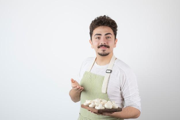 Portret van mannelijke kok die rauwe champignons op wit toont