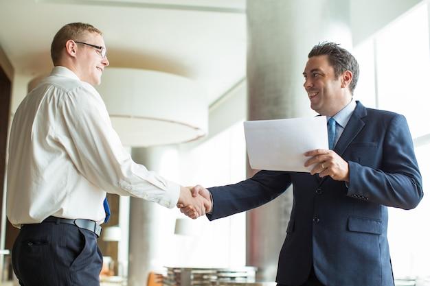 Portret van mannelijke partners die handen schudden op vergadering