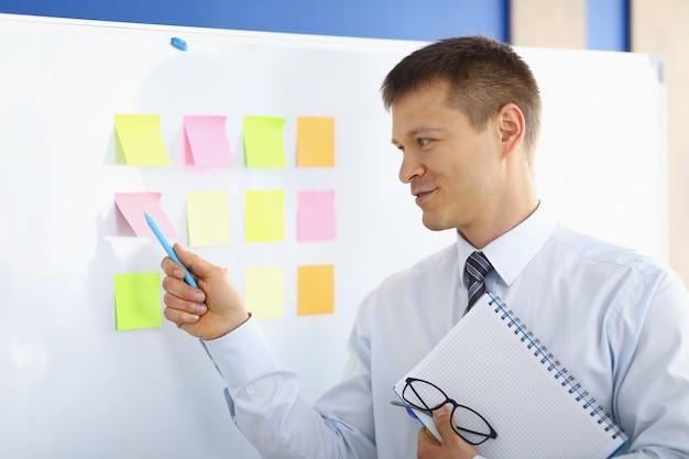 Portret van mannelijke persoon aanwijspen op kleurrijke notities op markeringsbord